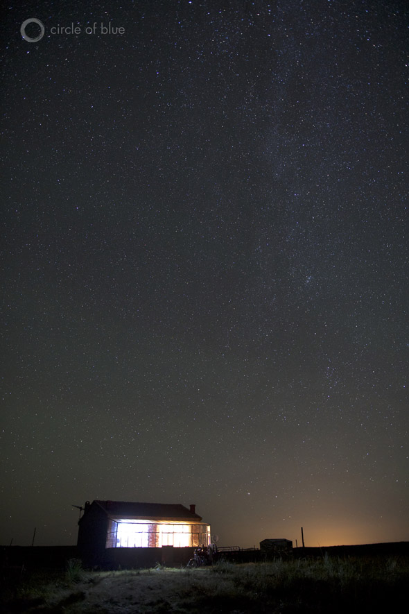 The Milky Way casts a glow over a farmhouse on the grasslands.