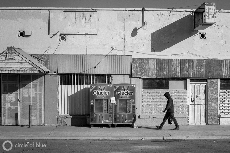 A man passes water vending machines in the small farmworker community of Stratford in California's Central Valley.