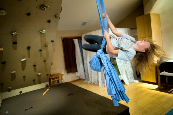 Laela Janssen swings from a sheet on the family's indoor climbing wall. Her mother Ginger was once a competitive climber.