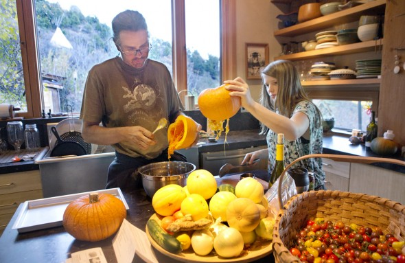 Robb Janssen and his daughter Lily gut pumpkins that were grown in their garden to make pumpkin pie from scratch. The teepee that Robb and his wife Ginger once lived in can be seen outside the hill.