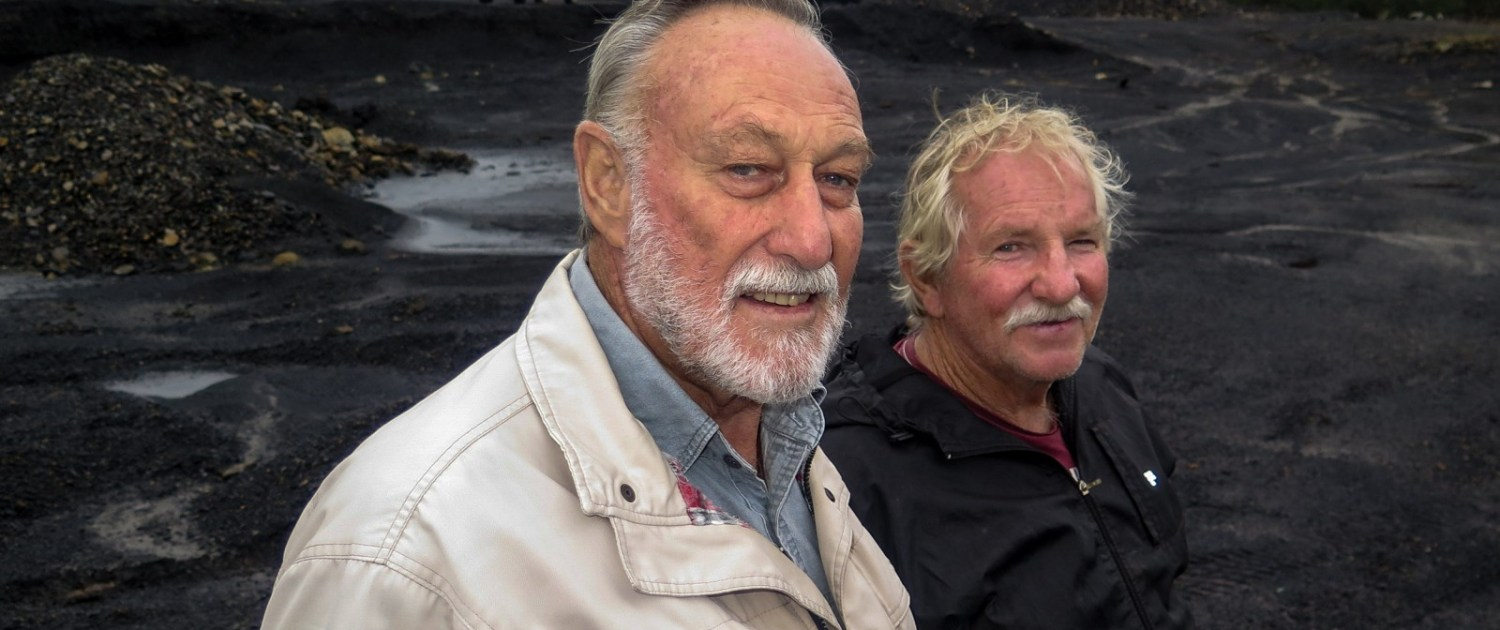 """At the site of an abandoned coal mine near Vryheid, Gerrie Beukes (left) and Hugo Joubert (right) explain the damage to land and water that occur at unreclaimed mines. """"I'll fight any new mine with everything I have. It's just a mess,"""" Beukes said. Photo © Keith Schneider / Circle of Blue"""