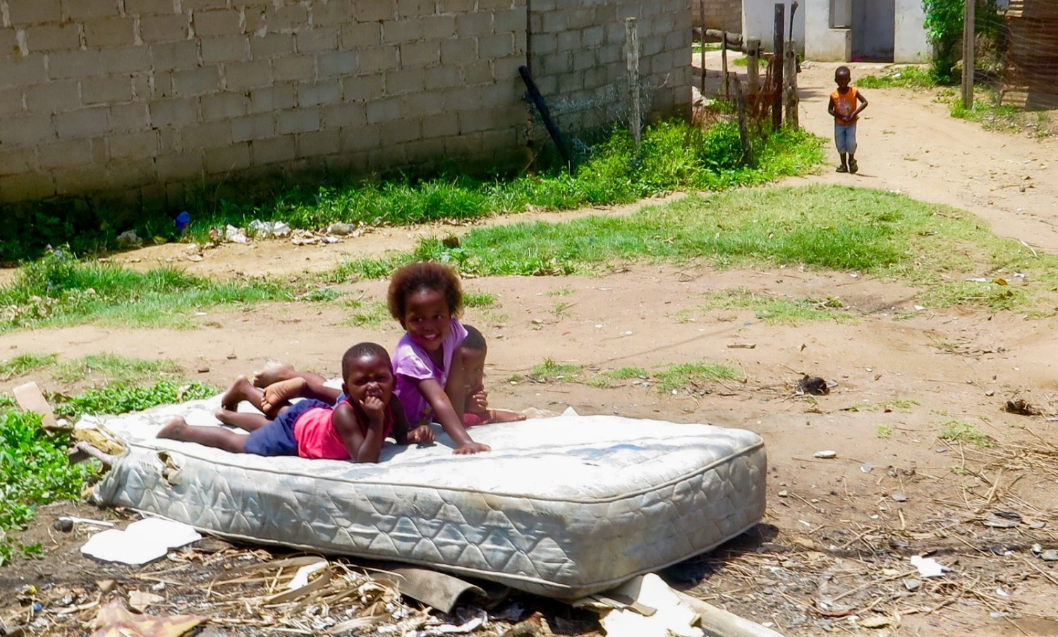 Children playing on a mattress at an informal settlement in Durban.