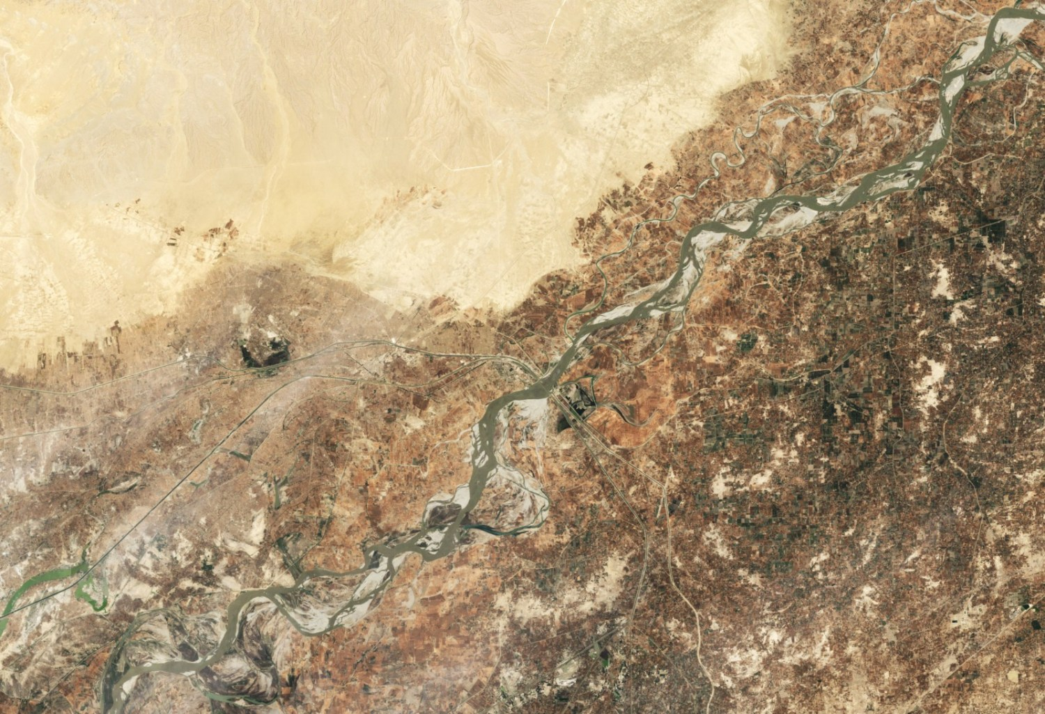 The Indus River is critical for agriculture and energy production in India and Pakistan. The shared river basin is home to at least 300 million people, and its water resources have long been a point of contention between the two countries. This image, captured by the Landsat 5 satellite in June 2009, shows the area around the Guddu Barrage, just south of the border between Punjab and Sindh provinces in Pakistan. Image courtesy NASA