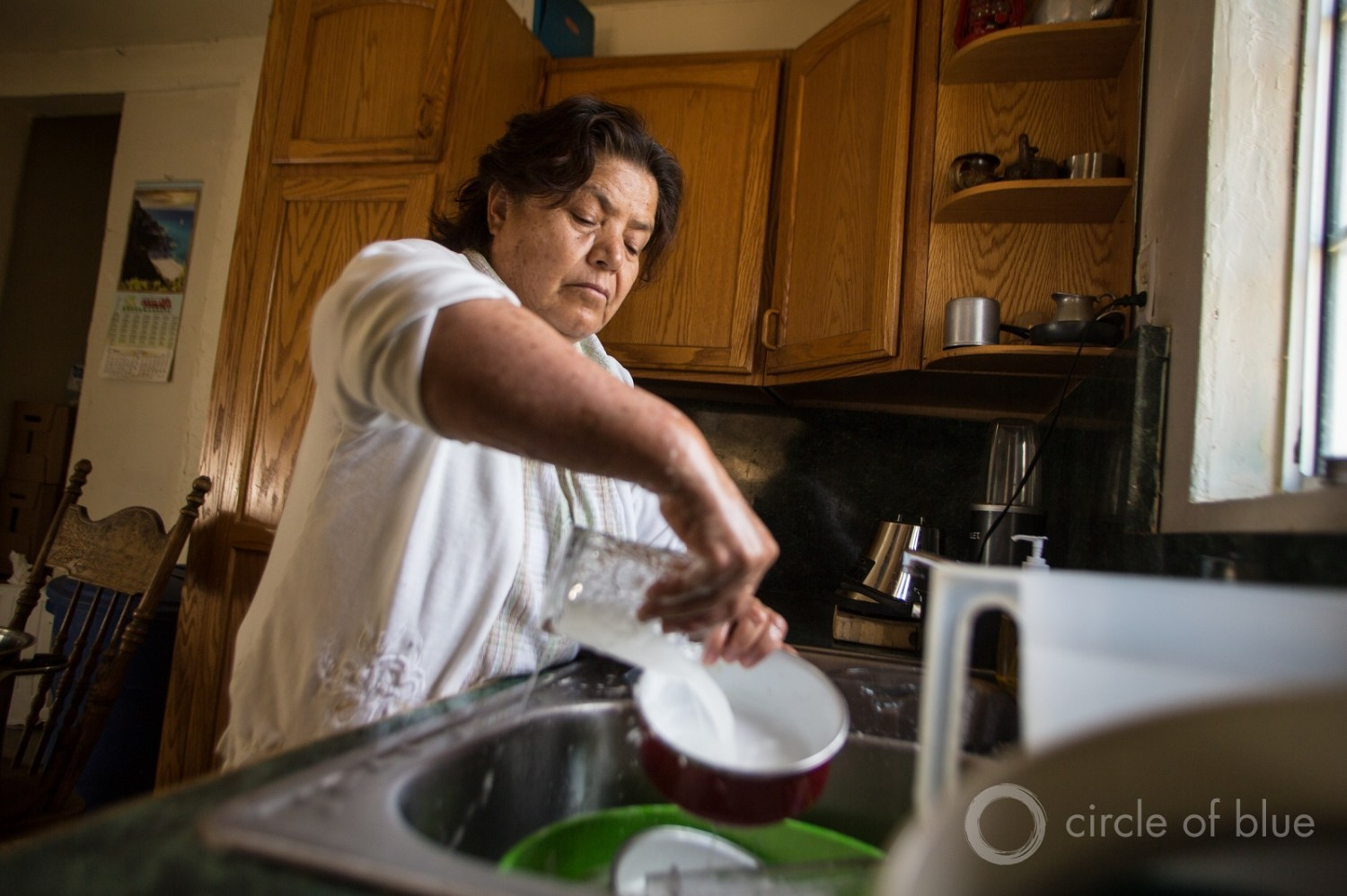 Belan Ruia makes every drop of water count as she washes dishes in April 2015 in her East Porterville, California, home. Like her neighbors, her well went dry during the state's historic drought. She and her husband, Artemio, got water from a nearby fire station. Photo © J. Carl Ganter / Circle of Blue
