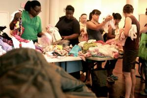 People sorting through baby clothing at common sharing event.
