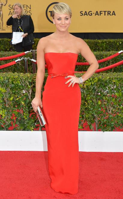 Kaley Cuoco usa vestido longo tomara de caia vermelho e cinto fino também vermelho
