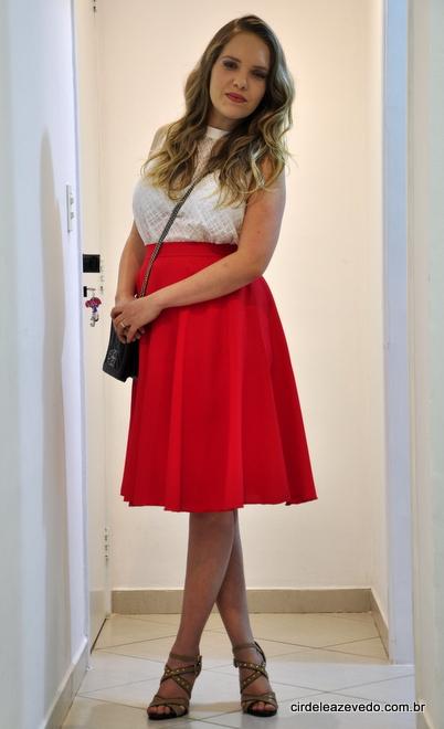 Eu usando saia midi vermelha, blusa branca, bolsa preta com alça de corrente e sandália bege com preto e tachas