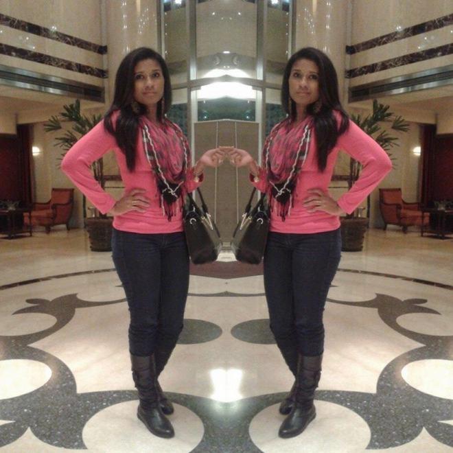 Dorinha veste calça jeans escuro com blusa rosa, lenço rosa com estampa, bota de cano longo e bolsa preta