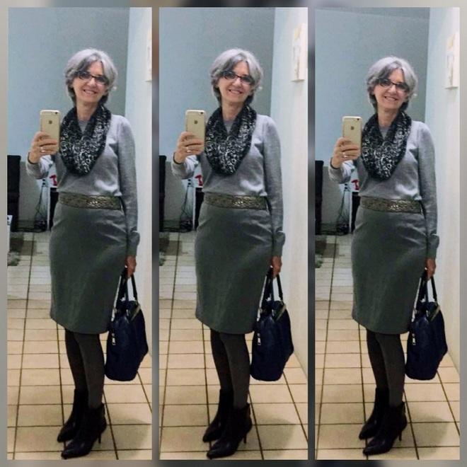 Maragareth veste blusa cinza e de mangas compridas, com o toque do lenço estampado preto e cinza. Saia lápis na cor cinza; cinto prata; meia fio 40 na cor chumbo; bolsa e bota de cano curto pretas.