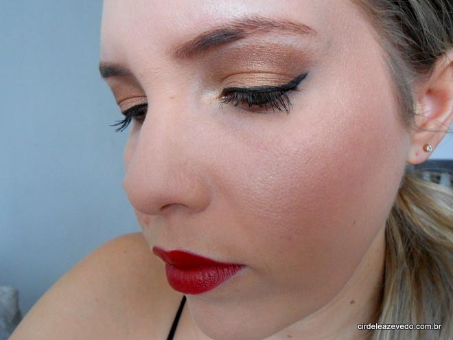 Eu usando maquiagem de marrom, dourado e bronze nos olhos, além de delineado gatinho, iluminador e batom vermelho