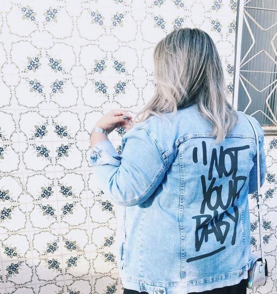 """Detalhe das costas da jaqueta onde se lê """"not your baby"""""""