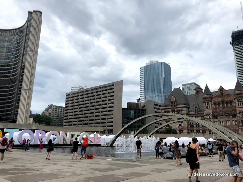 Vista da Nathan Phillips Square, em Downtown, com o letreiro escrito Toronto à esquerda