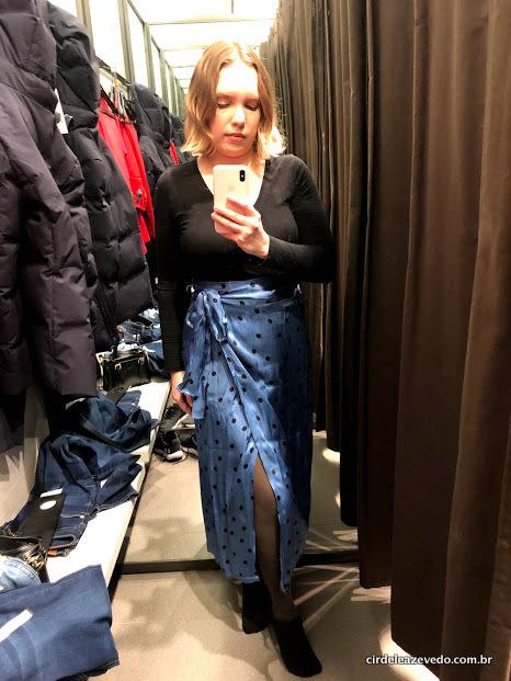 Eu usando blusa de mangas compridas preta com saia pareô azul de bolinhas pretas
