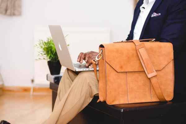 Business man typing on laptop.