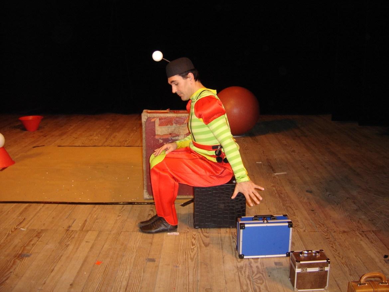 Un artiste assis sur une valise essaye d'attraper une autre valise Cirkonflex