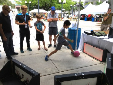 Kid kicking ball at skill court