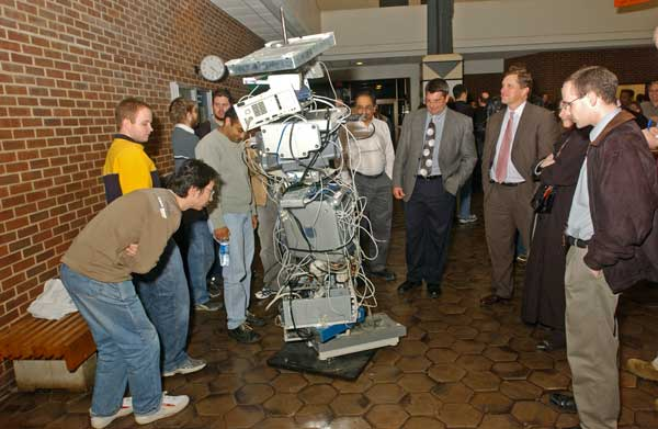 students standing with a sculpture made of computer parts