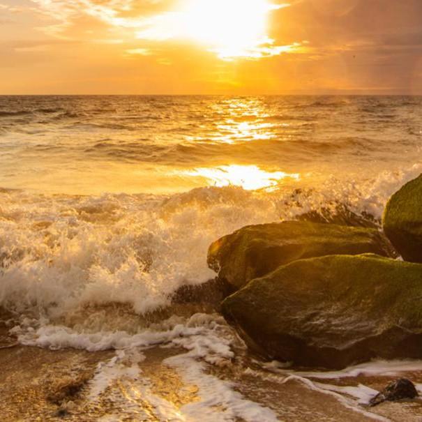 The ocean waves crashing into rocks at Cape Henlopen Beach