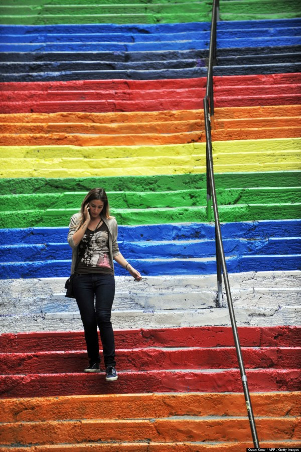 A Turkish woman takes pictures of rainbow-colored stairs on August 31, 2013 in Istanbul. Stairs in the Cihangir and Findikli neighborhoods, which attracted attention after being painted in rainbow colors by a local man on August 27, were all painted grey on the night of August. 29, and following comments on social media, the municipality of Beyoglu immediately painted them again in rainbow colors. Photo ©  Ozan Kose / AFP / Getty Images)