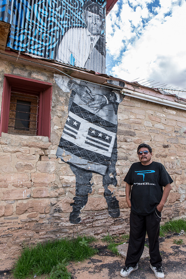 """Lorenzo Fowler owns the Old Red Lake Trading Post in Tonalea, AZ. On the wall is an image of his uncle, a respected Navajo Code Talker and Medicine Man who lived to the age of one hundred and one. """"Chip's images remind our youth of our culture. It's important"""", Lorenzo says. His uncle's picture is a dialogue-opener: """"Many people stop by to ask about it"""". Those people included us, travelers from Finland. Photo © Maria Jain"""