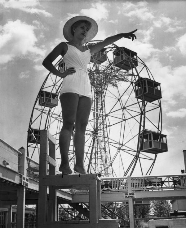 """""""A lifeguard at Steeplechase park, Coney Island stands with a whistle between her lips as she points to a transgressor in the pool below. In the background is a fairground big-wheel. July 1961.""""(Getty)"""