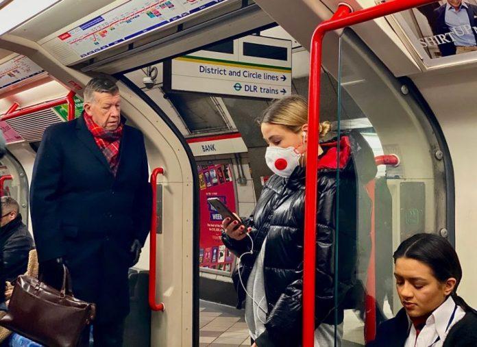 Brits don coronavirus face masks (and Tesco bags) on public ...