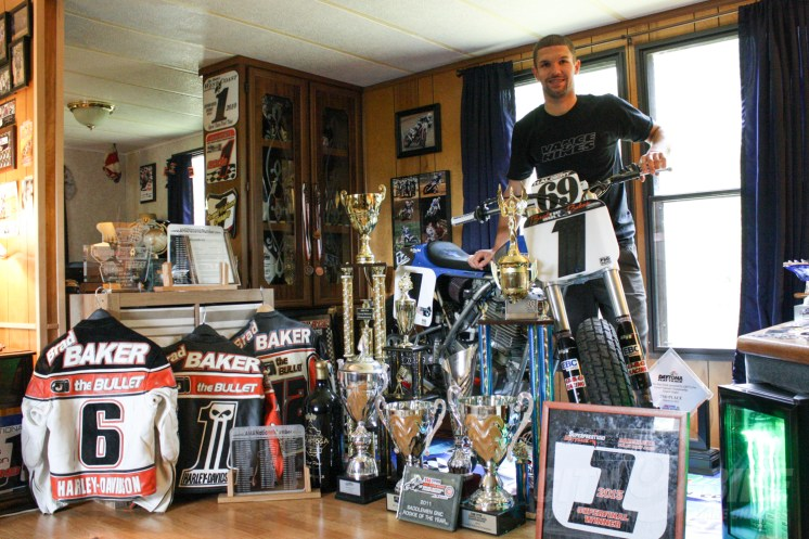 Brad in his living room with a Rotax framer and leathers from previous seasons.