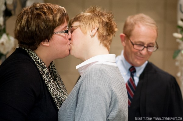 Hobart couple Michelle Davies, on left, and Tonya Richards kiss as Lake Superior Court judge John Pera stands near after performing their marriage ceremony on Tuesday at the Lake County Clerk's office. | Kyle Telechan/For Sun-Times Media