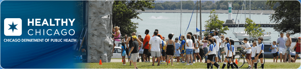 A bunch of children and adults by the lake in a park practicing mountain climbing