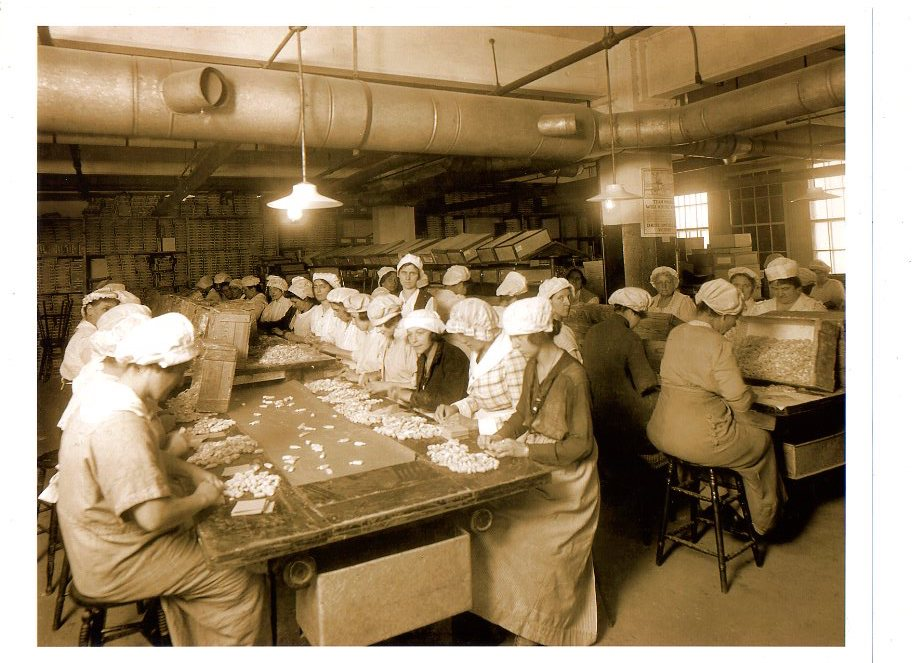 Female employees wrapping candies at large tables in a factory for Wallace Candies in 1914.