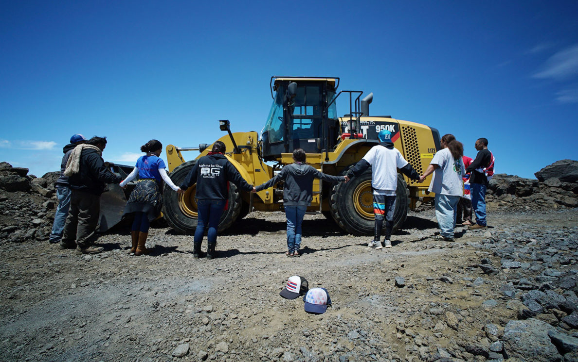Kahookahi Kunuha leads a small group of supporters near a tractor on the TMT site on the summit of Mauna Kea. 10 april 2015. photograph Cory Lum