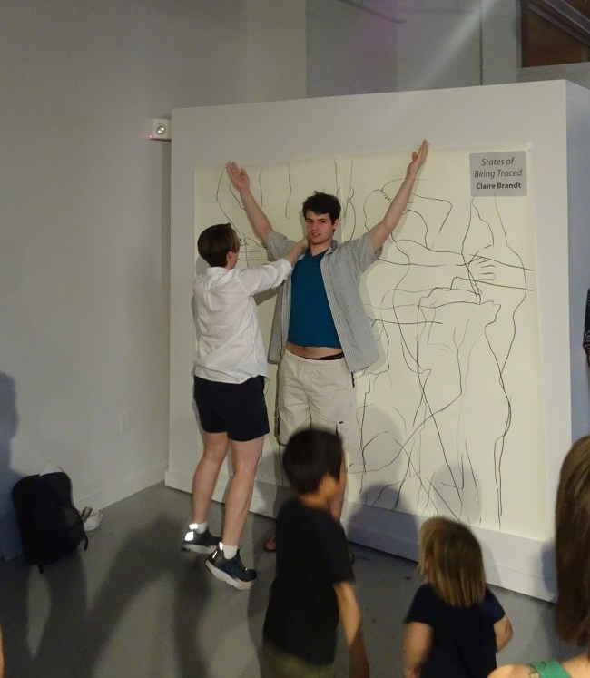 artist tracing outline of young man in performance art