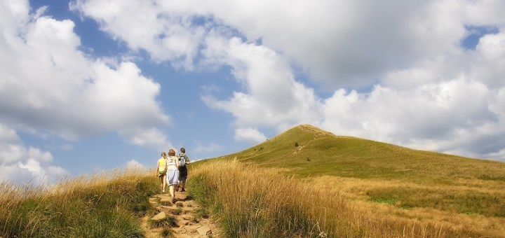 Image of mountain, three people walking up a pathway. Blue sky in background.
