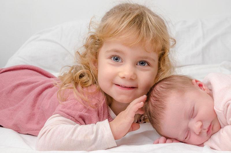 Une petite fille blonde aux yeux bleus fait un calin à un bébé endormi