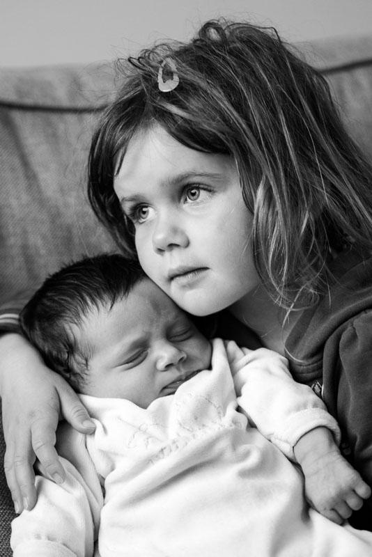 portrait en noir et blanc d'une fille tenant sa petite soeur dans les bras