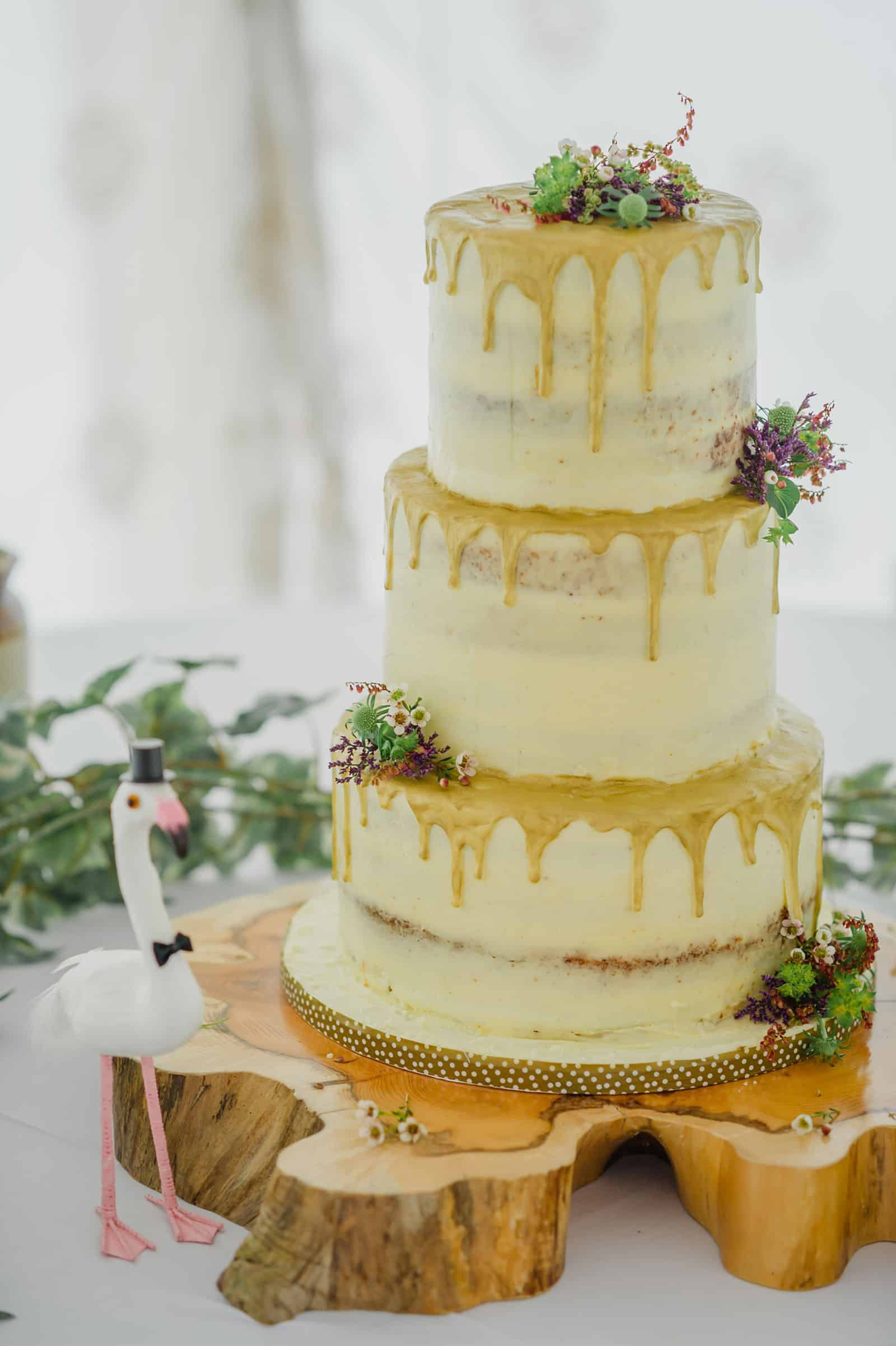 semi naked wedding cake with gold drips and fresh flowers