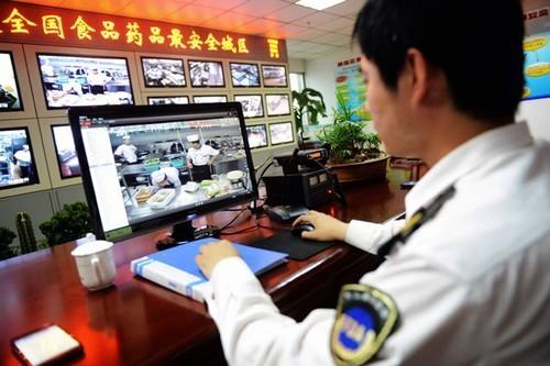Na central de monitoramento, fiscal observa cozinheiros trabalhando em restaurante