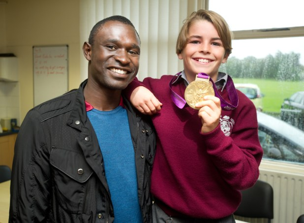 Olympian David Rudisha has his medal examined by pupil Zach Whelehan during his visit to Ennistymon CBS  on Tuesday. Photograph by John Kelly