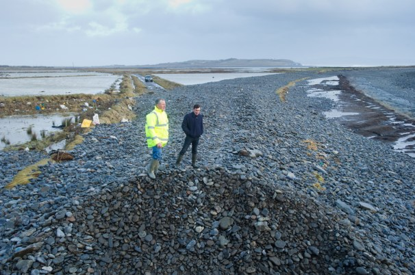 Farmers  Vincent Hedderman and Matthew Carmody of Rahona, Carrigaholt, examine the road between Rahona and Kilbaha where the sea covered the road. Photograph by John Kelly.