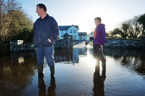 Tom Nolan and his son, Brian, outside their house at Kiltartan, where the floodwater continues to rise and the public road is blocked.