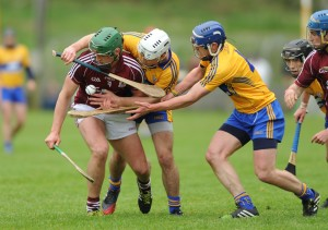Galway's Niall Burke is tackled by Clare's Stephan O Halloran and Conor Cooney during  the challenge game as part of the Kilmurry Ibrickane GAA Club 100th anniversary celebrations. Photograph by John Kelly.