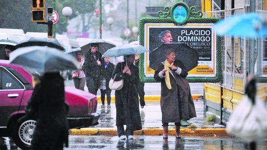 FIEL EN EL CARTEL. ENTRE PARAGUAS, LA IMAGEN DEL TENOR ESPAÑOL SE PROYECTA EN LA CALLE; EL CLIMA TAMPOCO CONTRIBUYO CON EL CONCIERTO.