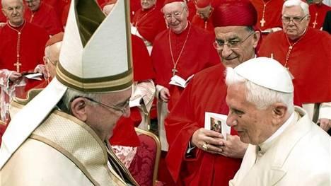 Francisco saluda al Papa emérito, en segundo plano detrás de Benedicto está el cardenal Bernard Law de Boston.  (Reuters)