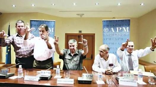 Gestos. los ex prisioneros cubanos levantan sus brazos y hacen las  señales de la libertad y la victoria.
