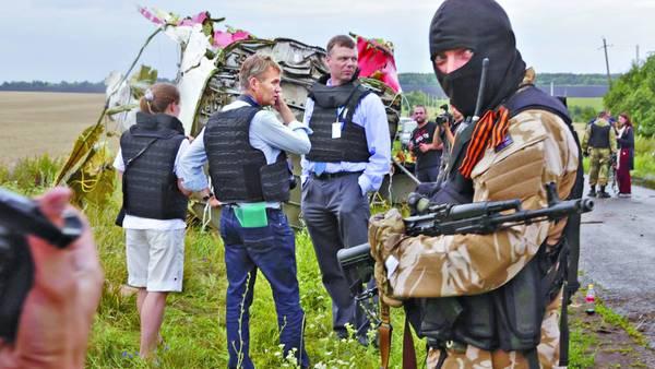 Inspección. Un grupo de técnicos protegidos por patrullas rebeldes comienzan la investigación en el lugar donde cayeron los pedazos del Boeing de Malaysia Airlines abatido por un misil / REUTERS