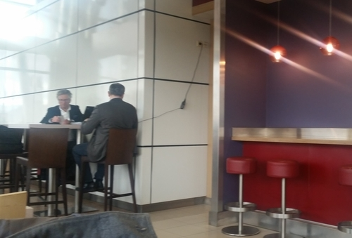 Slapdash design: businessmen with laptop plugged in inconveniently