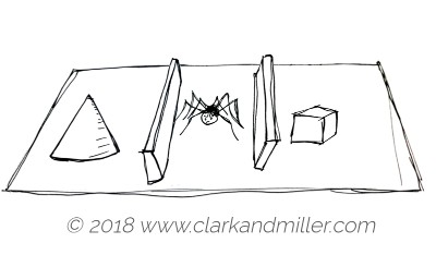 A cone, a spider and a cube on a table with walls on each side of the spider