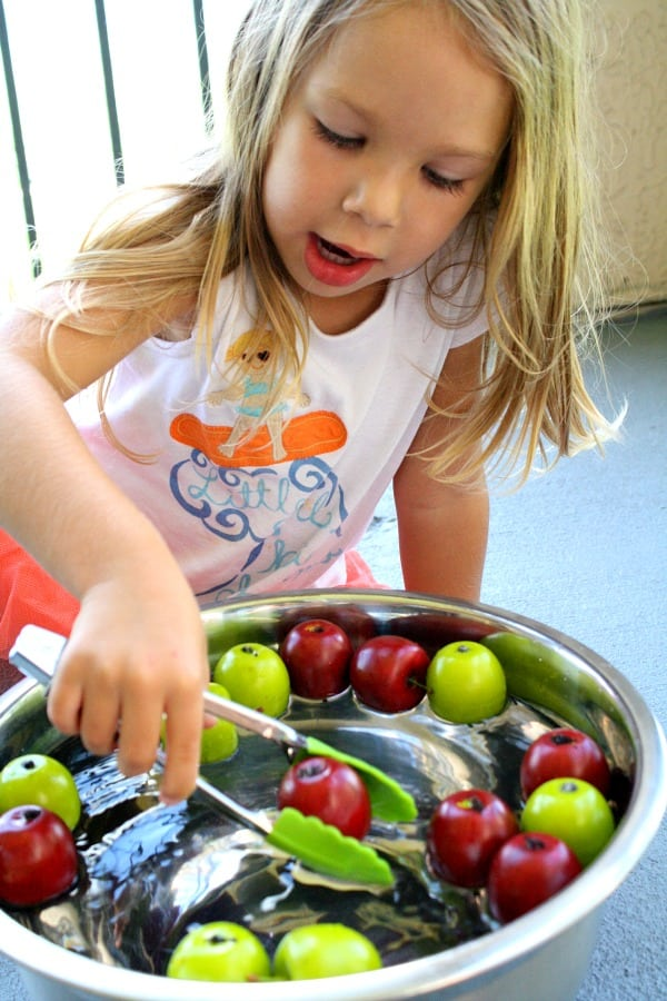 A little girl in front of a bowl of fruit, with Apple and School