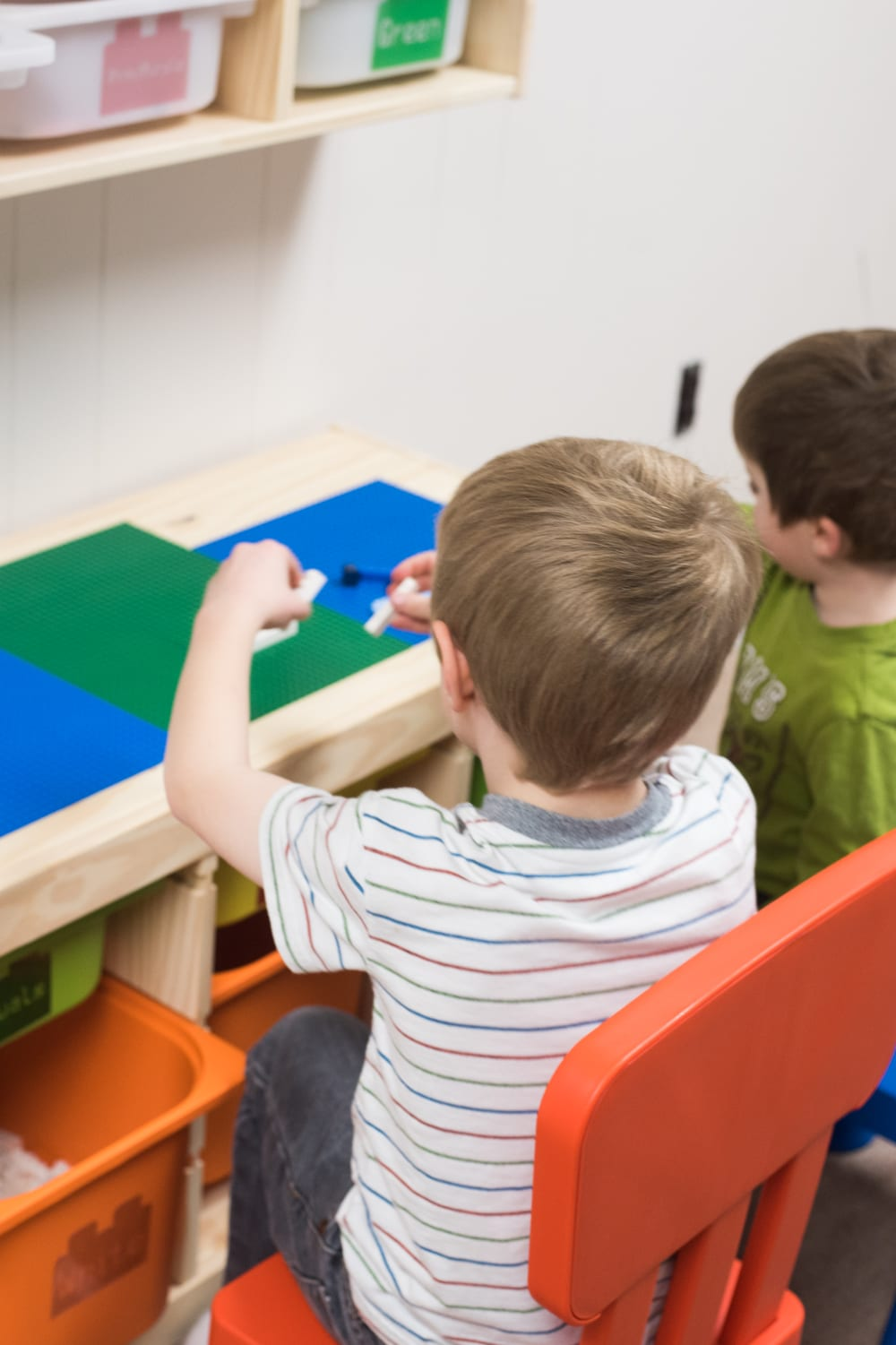 child sitting at lego table