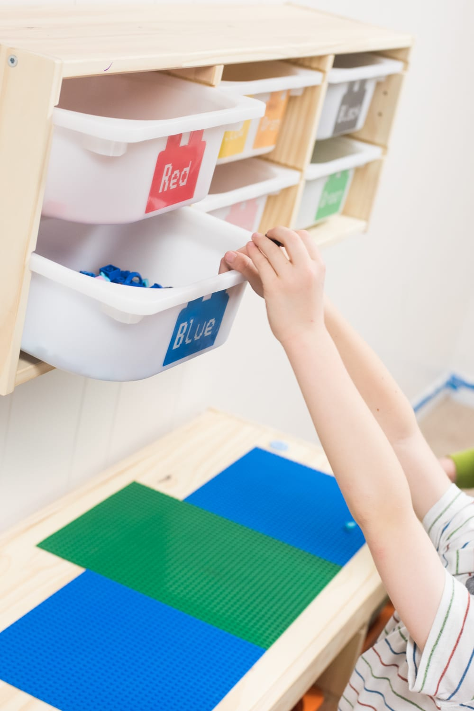 Child reaching for lego bin